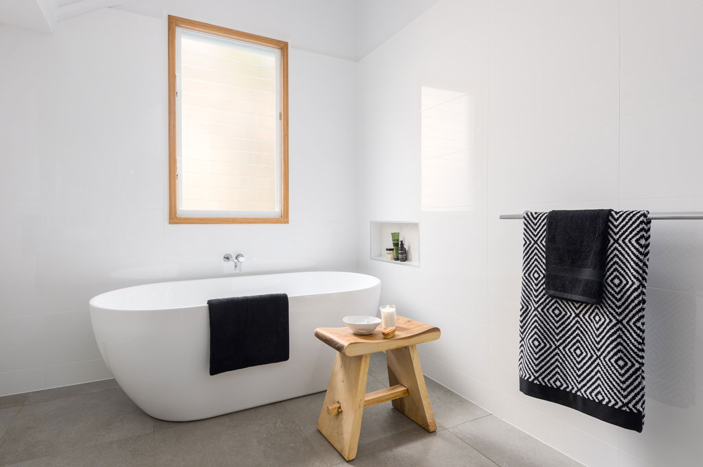 Bathroom Renovation Brisbane White Modern Style Shower Bath with a wooden chair next to it